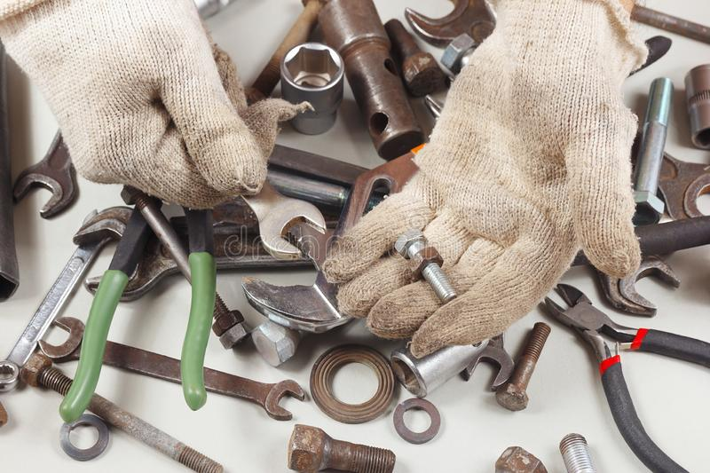 Hand of serviceman in gloves repairing parts of mechanism in workshop royalty free stock photo