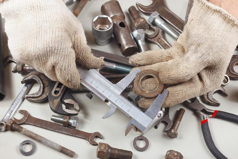 Hand of serviceman measure the part with calliper in workshop stock images