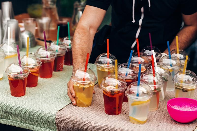 Hand serving lemonade with mint and lemons, space for text. street food festival. drink bar at reception, catering outdoors. Summer picnic. colorful drinks in stock image