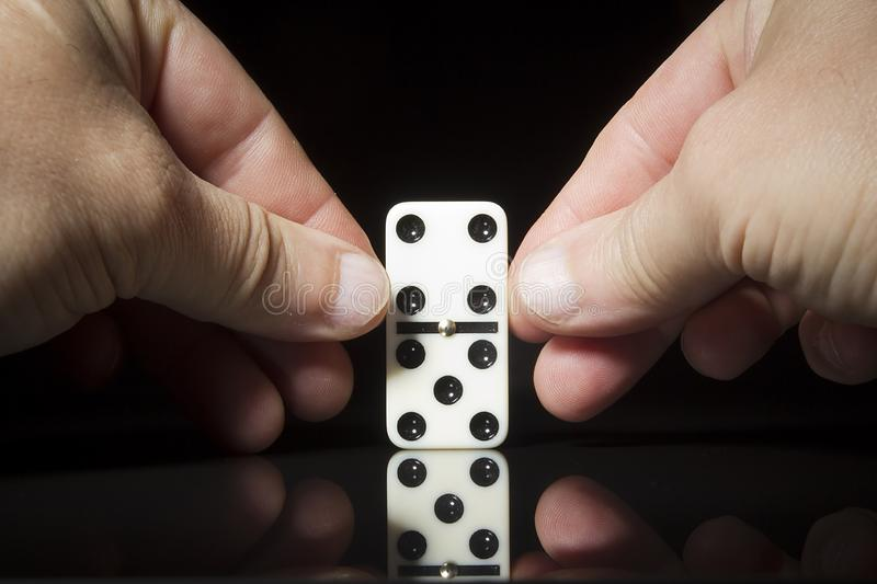 The hand sets the dominoes royalty free stock photos
