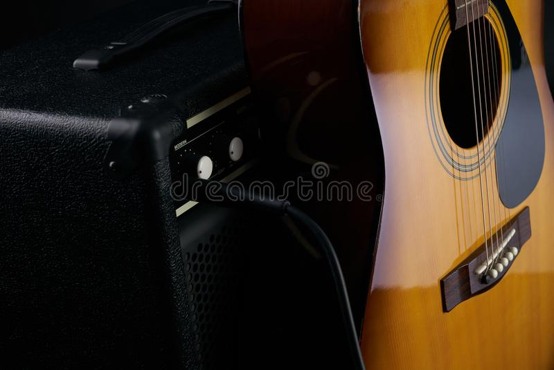 Hand setzt akustische klassische Gitarre zum kombinierten Verstärker stockfotos