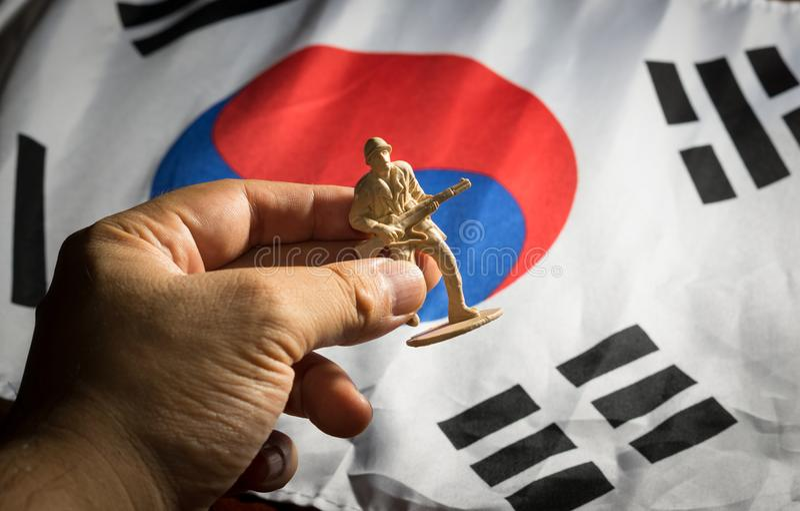 Hand setzte Soldatspielzeug zu Korea-Flagge lizenzfreies stockbild