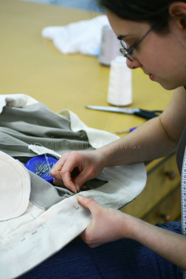 Hand sewing. Girl hand finishing a trousers royalty free stock photography