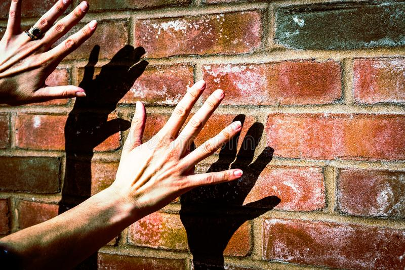 Shadow Hands on brick wall sunny. Hand shadows in fron ot brick wall maximum contract epic exoosure royalty free stock photos