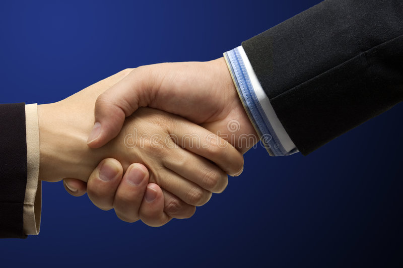 Hand shake. In front of a blue background - CLIPPING PATH INCLUDED for easy isolation