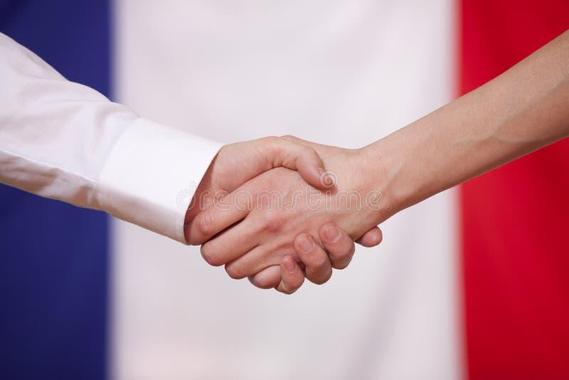 Hand shake over france flag. Diplomacy agreement stock image