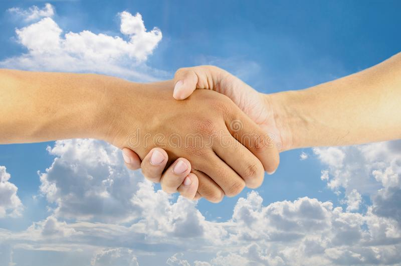 Hand shaking on blue sky background. Two hand shaking on blue sky background stock images