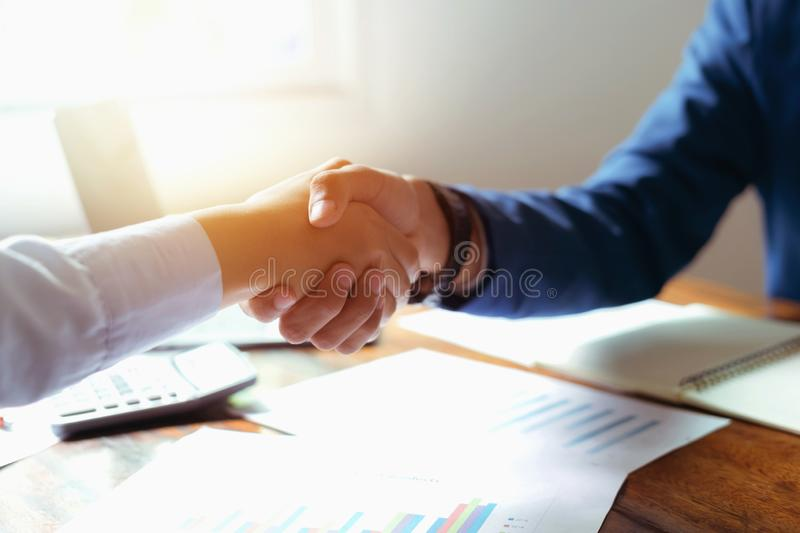 Hand shaking after meeting finish in office. Desk, two, accounting, analysis, product, designer, entrepreneur, merchandise, handshaking, interaction, chart royalty free stock photo