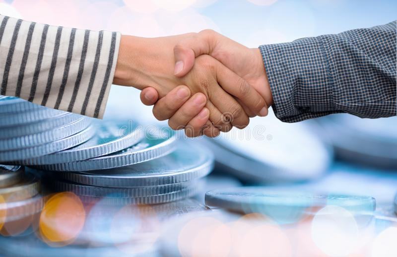 Hand shaking over coin and bokeh background,Business success or. Teamwork concept stock photos