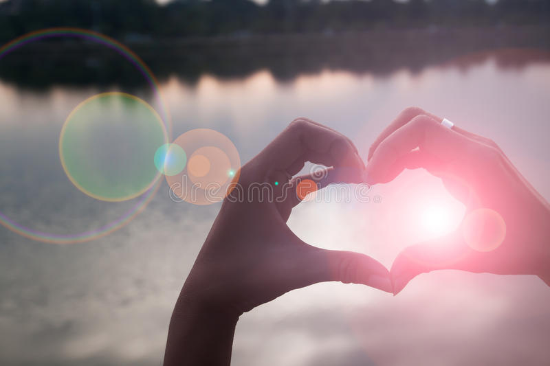 Hand in shape of love heart. With sunset reflaction background stock photography