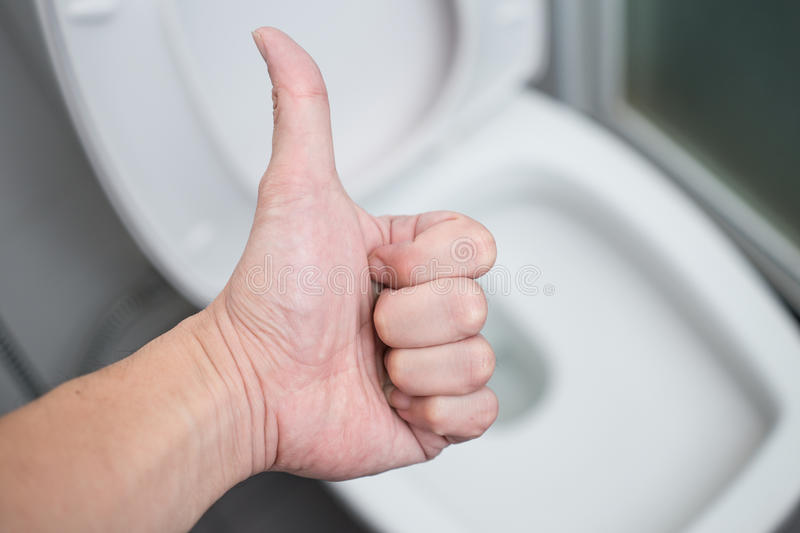 Hand show sign Good Thumb Up with clean Toilets Bathroom Toilet Seats. Hand show sign Good Thumb Up with background cleaning Toilets Bathroom Toilet Seats or royalty free stock photos