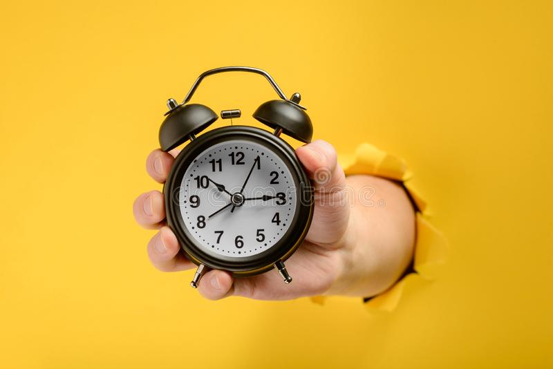 Hand showing an alarm clock stock images