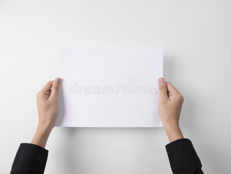 Hand showing blank paper A4 flyer for mockup template logo brand. Ing on grey background royalty free stock photo