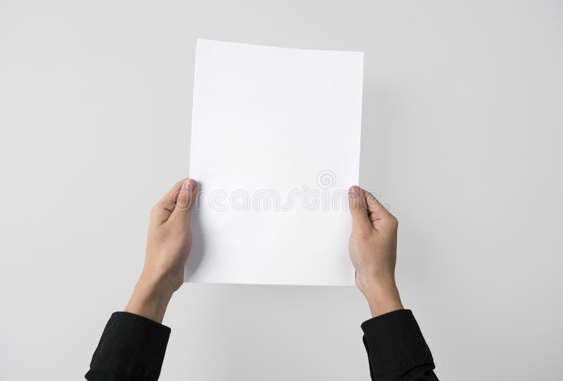 Hand showing blank paper A4 flyer for mockup template logo brand. Ing on grey background royalty free stock photos