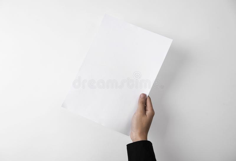 Hand showing blank paper A4 flyer for mockup template logo brand. Ing on grey background royalty free stock images