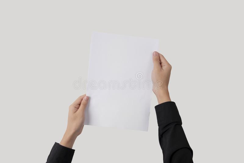 Hand showing blank paper A4 flyer for mockup template logo brand. Ing on grey background royalty free stock photography