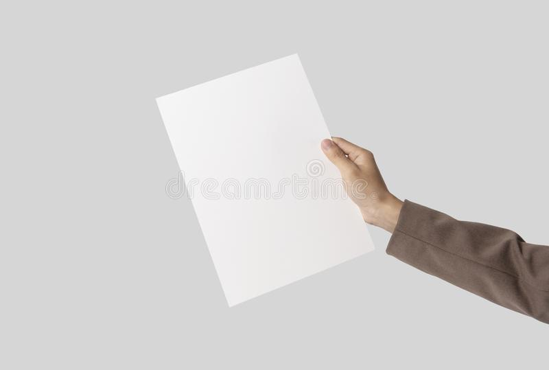 Hand showing blank paper A4 flyer for mockup template logo branding on grey background.  stock photography