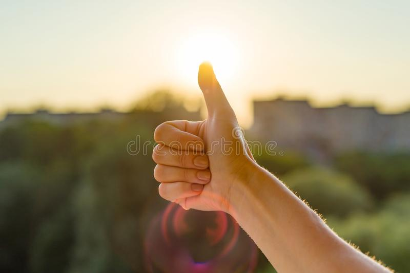Hand showing gesture of the thumbs up, the sign symbol is ok okay good. Background sunny urban sunset. stock image