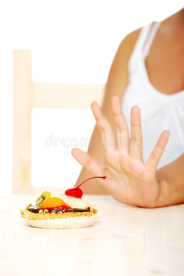 Hand showing stop gesture to cake. stock image