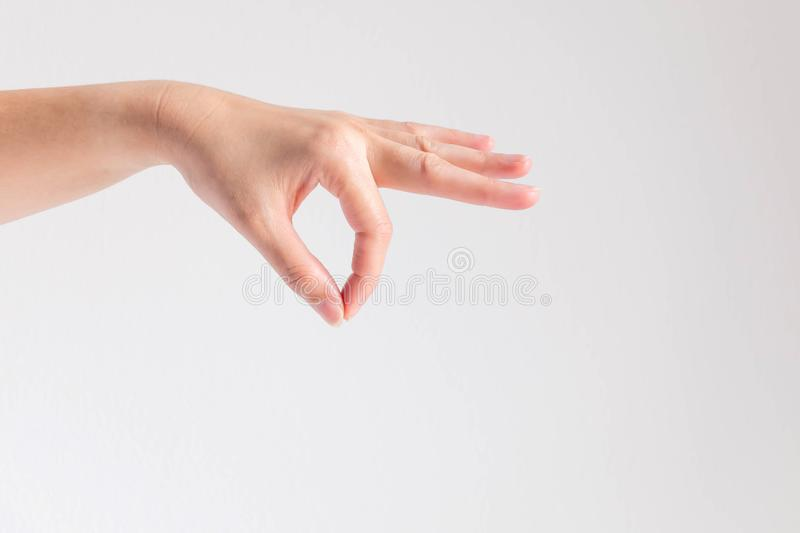 A hand of woman posturing thumb and forefinger touch together and other finger stretch forward on white background. A hand showing thumb and forefinger touch royalty free stock photo