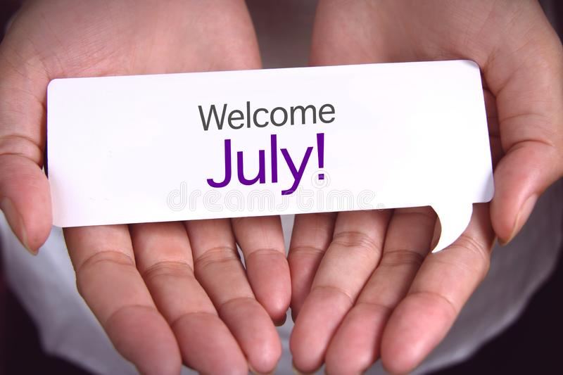 Hand showing welcome July stock photos