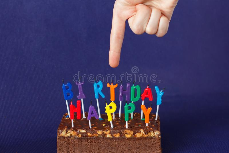 Hand Shows Happy Birthday Brownie Cake with Peanuts, Salted Caramel and Colorful Unlighted Candles on the Violet Background. Copy space celebration sweet fire royalty free stock image