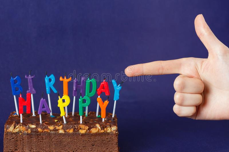 Hand Shows Happy Birthday Brownie Cake with Peanuts, Salted Caramel and Colorful Unlighted Candles on the Violet Background. Copy space celebration sweet fire royalty free stock photography