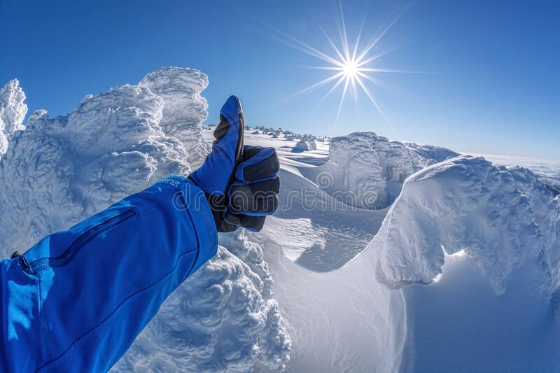 Hand shows thumbs up against winter landscape stock photography