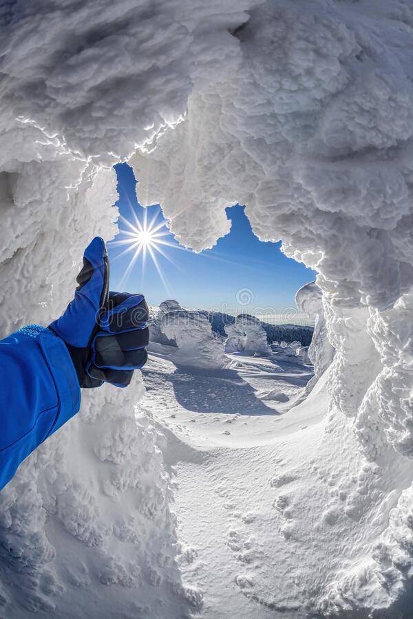 Hand shows thumbs up against winter landscape stock image