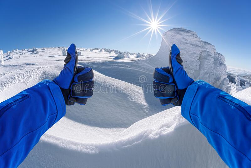 Hands shows thumbs up against winter landscape royalty free stock photography