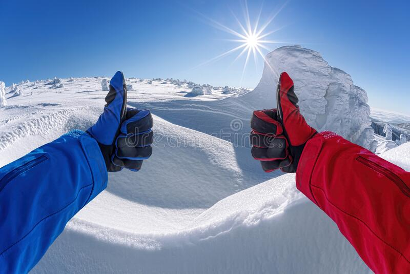 Hands shows thumbs up against winter landscape stock photography