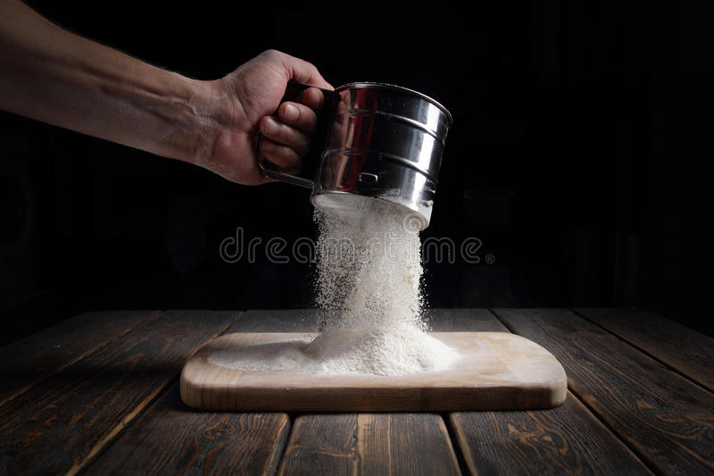 Hand sifts the flour through a sieve. Food royalty free stock image