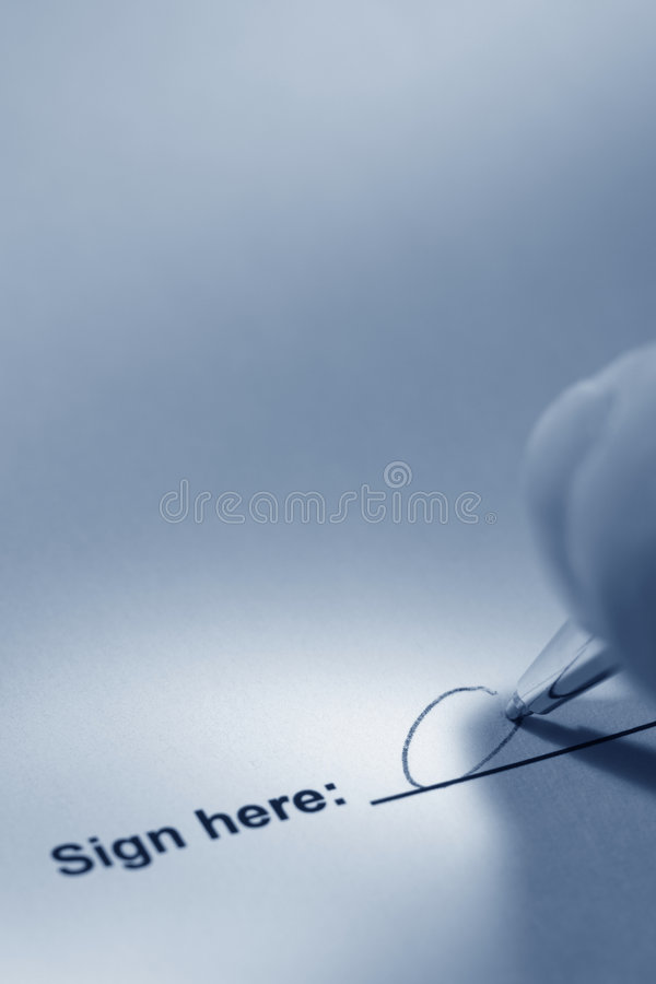 Hand Signing a Document with Pen on Sign Here Line stock photo