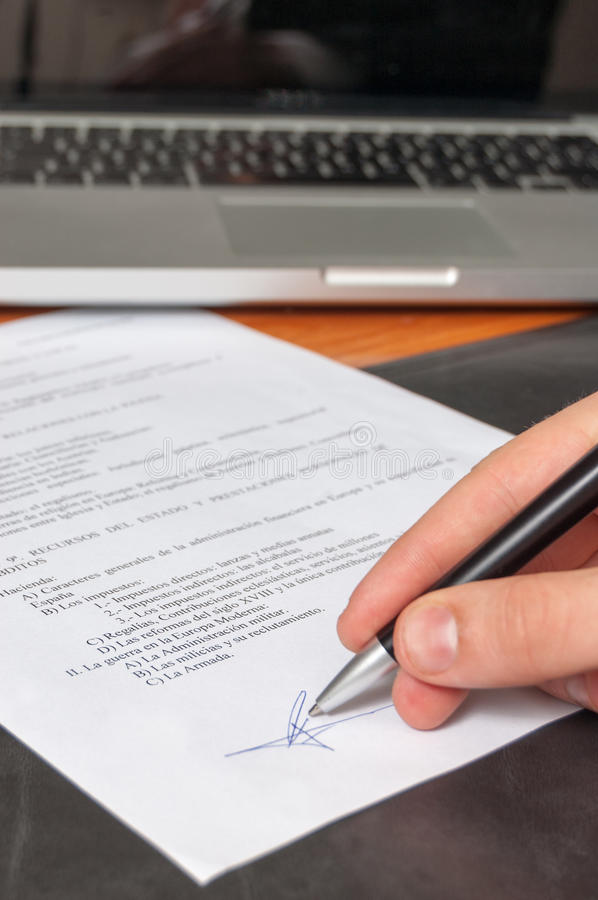 Hand signing documents. Hand signing a document on an office desk with a laptop in the background stock photography