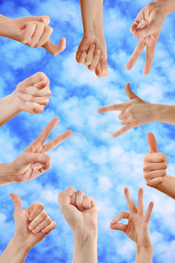 Hand signs. Various hand signs and symbols against a blue sky with clouds stock photos
