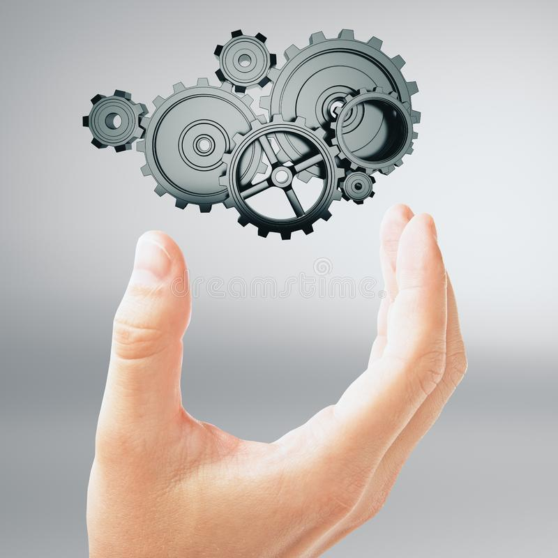 Business idea concept. Hand and silver metal cogwheel at grey background. 3D render stock photos