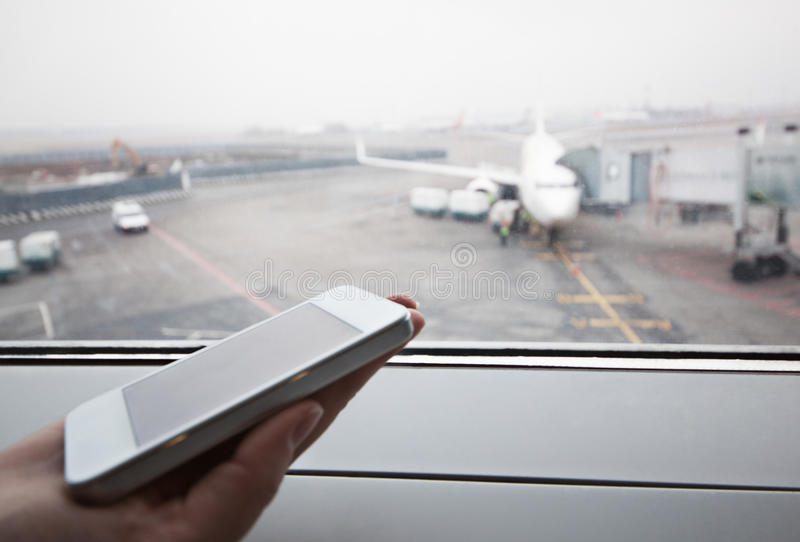 Hand with smart phone by the window at airport. Close-up shot of female hand holding smart phone by window at airport. Area with airplane in background royalty free stock image