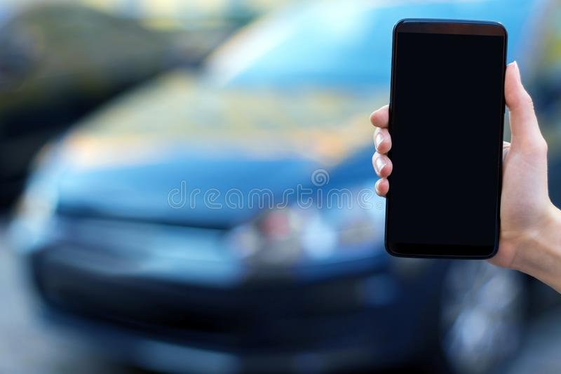 Hand with smartphone on street with new car royalty free stock image