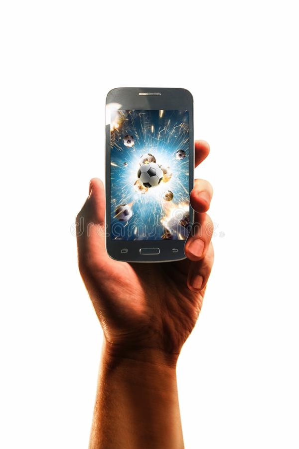 Hand with a smartphone on which soccer balls, white isolated royalty free stock photo