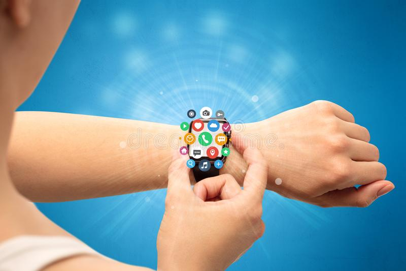 Smartwatch with application icons. Hand with smartwatch and application symbols nearby royalty free stock image