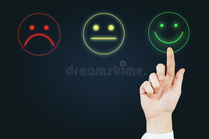 Great service concept. Hand with smiley rating on dark background. Great service concept royalty free stock photo