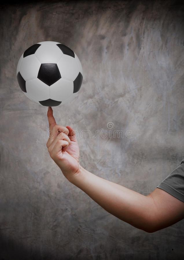 Hand and soccer football. In front of cemant wall background royalty free stock photography