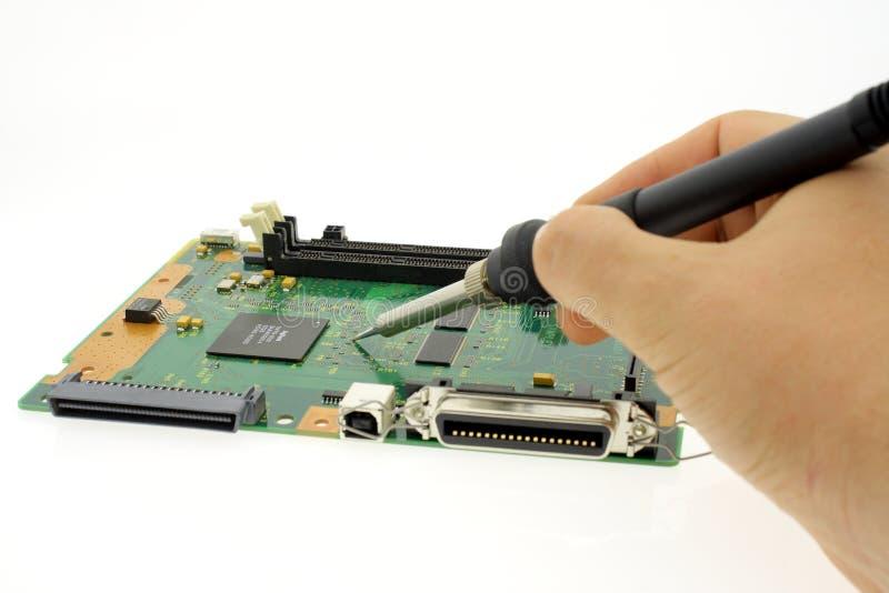 Hand solderend soldeersel van elektronika raad, reparaties, of productie royalty-vrije stock afbeelding