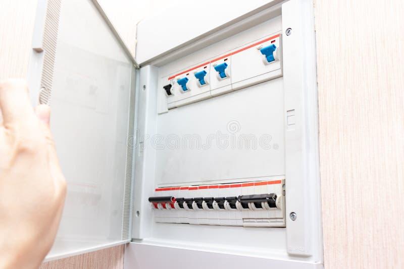 Hand som öppnar den elektriska skölden med automatiska strömbrytare av elektricitet i huset - elektricitetskontrollbord med ström arkivfoto