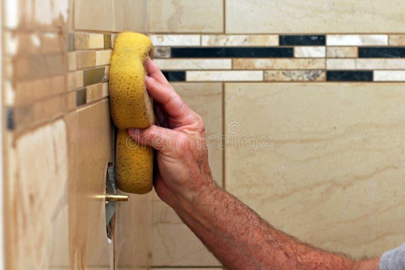 Hand som applicerar grout till väggtegelplattor royaltyfri fotografi