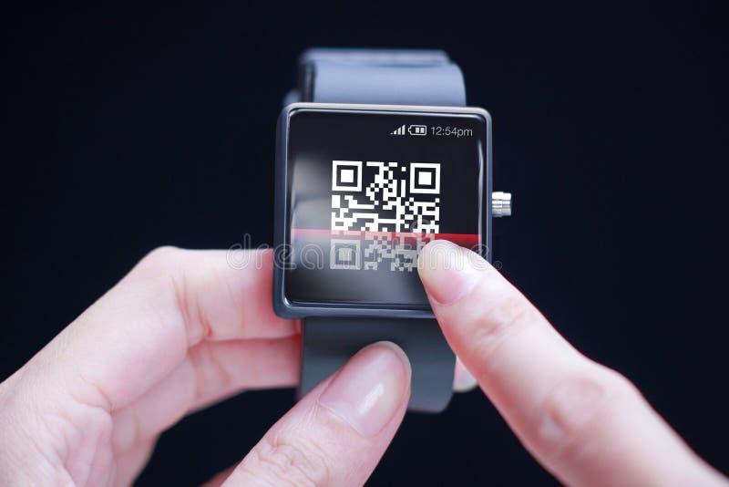 Hand som avläser QR-kod på smartwatch royaltyfri foto