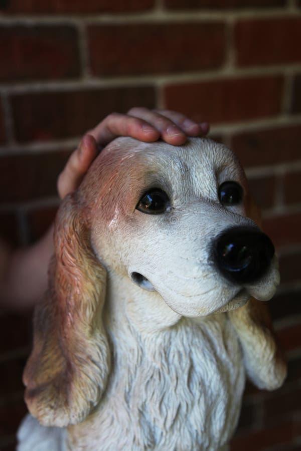 Hand som daltar en hundskulptur arkivfoton