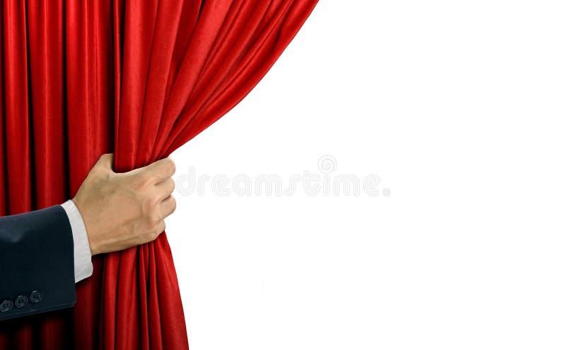 Hand som drar den röda gardinen för etapp royaltyfria foton