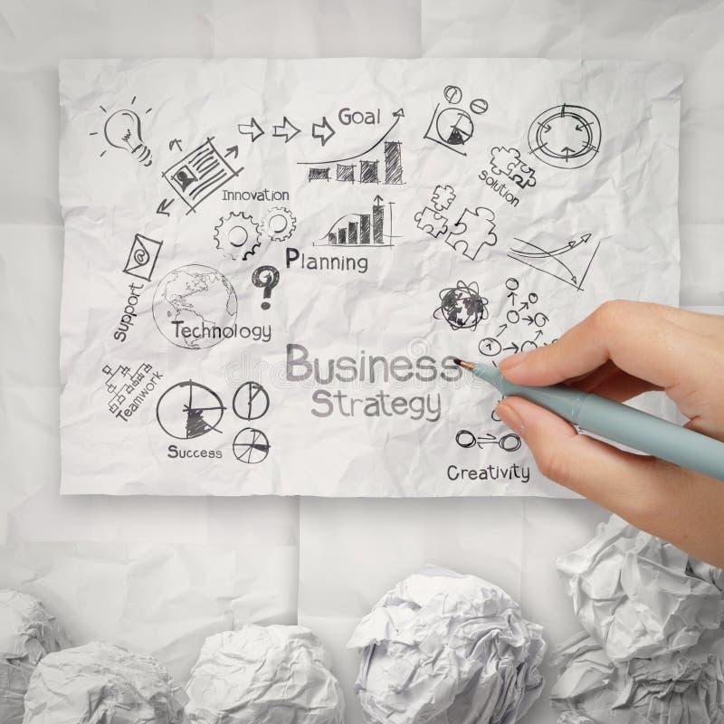 Hand som drar idérik affärsstrategi på skrynklig pappers- backgr arkivbilder