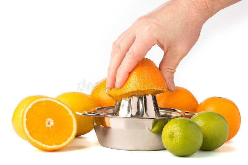 Hand som drar ut en apelsin i Juicer med hela citrusfrukter arkivbilder
